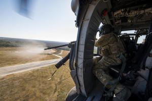 """Sgt. Uwemediimo Essien feuert die Bordwaffe im Kaliber .50 bei einem simulierten Angriffe auf ein Angriffsziel am 19. Februar 2015 auf dem Luftwaffenstützpunkt Moody. Die Waffe ist die Hauptverteidigungswaffe des HH-60G """"Pave Hawk"""". Hubschrauber und Besatzung gehören zum 41st Rescue Squadron, die bei Spezialmissionen eingesetzt werden. Bild: U.S. Air Force/Senior Airman Ryan Callaghan/Released Bildlizenz"""