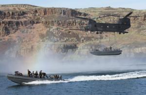 Angehörige des Special Boat Teams 12, sogenannte Special Warfare Combatant-craft Crewmen, aus dem kalifornischen Coronado am 21. Mai bei einer Übung mit Piloten des 4. Bataillons des 160. Special Operations Aviation Regiment von der Joint Base Lewis-McChord im Bundesstaat Washington bei einer Lufttransport-Übung auf dem Moses Lake in Washington. Bei einer solchen MEATS-Übung (Maritime External Air Transportation System) werden Wasserfahrzeuge von einem bestimmten Punkt an Land oder auf Gewässern mit einem MH-47G Chinook zu einem anderen Punkt transportiert. Dabei haken die Soldaten des Special Boat Teams das Wasserfahrzeug am Helikopter ein und klettern eine Sturmleiter zum Hubschrauber hoch. Am Absetzungspunkt benutzen sie dann das Fast Rope-Verfahren, um wieder in Boot zu kommen, bevor die Hubschrauberbesatzung das Kabel löst. Bild: U.S. Army/Sgt. Christopher Prows, 5th Mobile Public Affairs Detachment